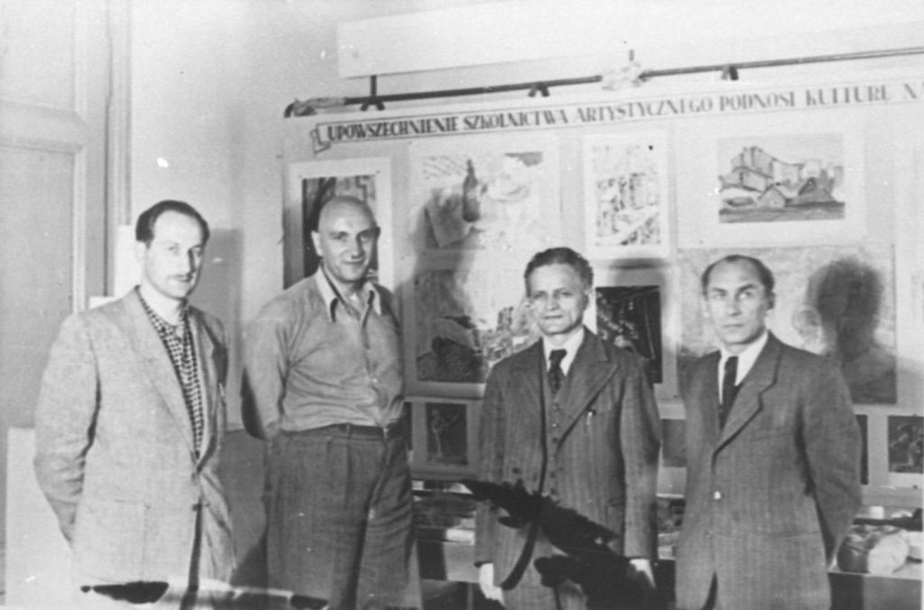 Organizatorzy wystawy (drugi od prawej Aleksander Ligaszewski – wykładowca PIRR). Wystawa pod hasłem: UPOWSZECHNIENIE SZKOLNICTWA ARTYSTYCZNEGO PODNOSI KULTURĘ
